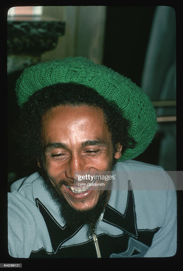 A close-up of Jamaican reggae musician Bob Marley laughing. He looks very relaxed and wears a green, crocheted cap over his dreadlocks.