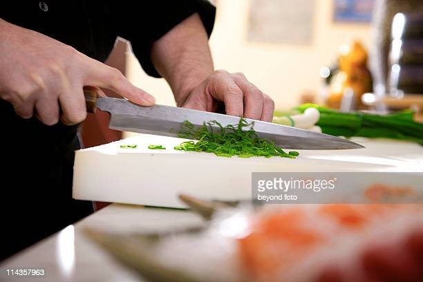 close-up of japanese chef cutting spring onions