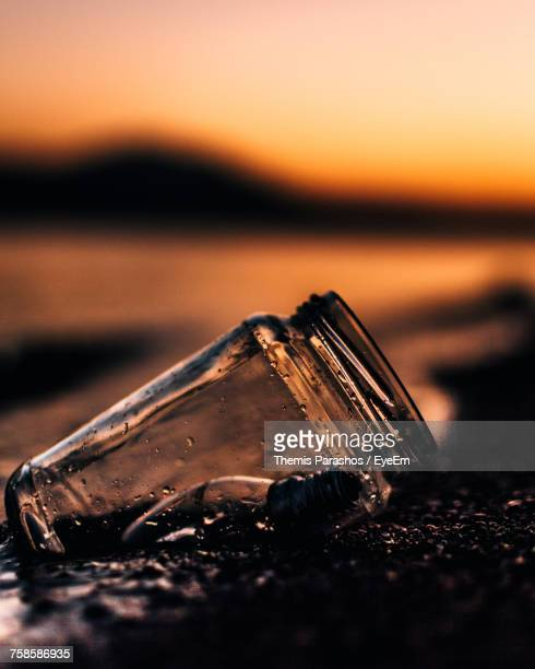Close-Up Of Jar On Shore At Beach During Sunset