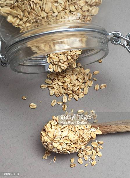 Close-up Of Jar Pouring Oats On Spoon And Table