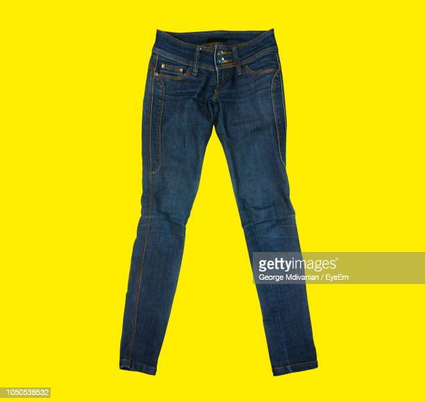 close-up of jeans against yellow background - trousers stock pictures, royalty-free photos & images