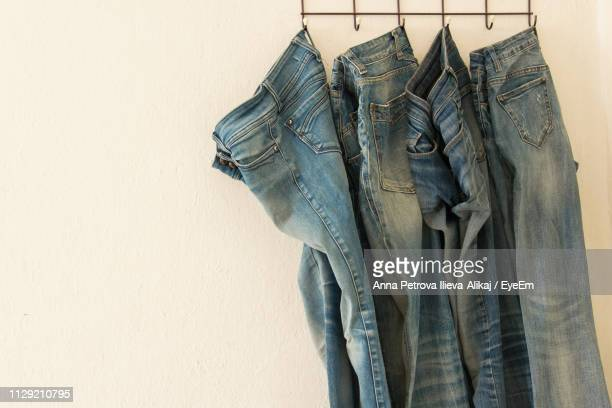 close-up of jeans hanging from rack - jeans stock pictures, royalty-free photos & images