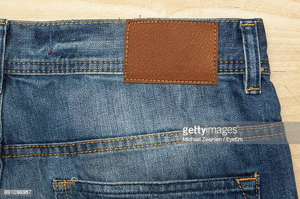 close-up of jeans on table for sale - jeans stock photos and pictures