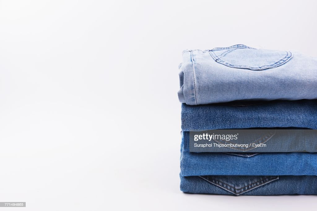 Close-Up Of Jeans Stacked Against White Background : Stock Photo