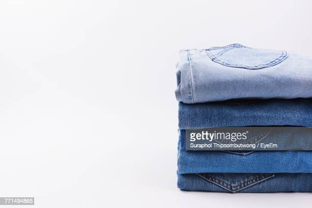 close-up of jeans stacked against white background - spijkerbroek stockfoto's en -beelden