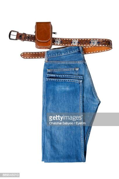 Close-Up Of Jeans With Belt Against White Background