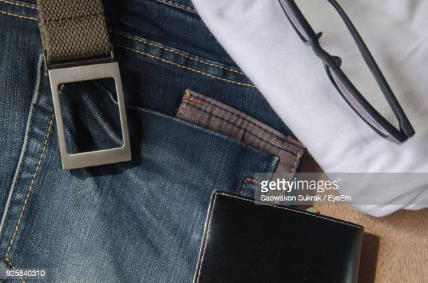 close-up of jeans with purse and eyeglasses on table - menswear ストックフォトと画像