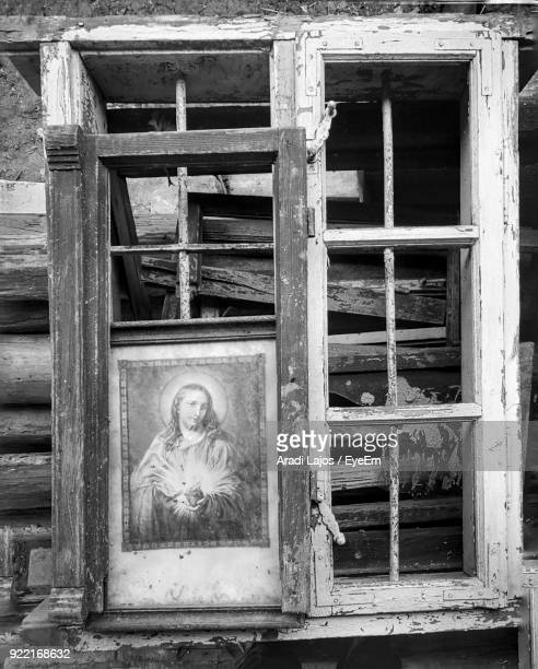 Close-Up Of Jesus Christ Painting On Abandoned Window