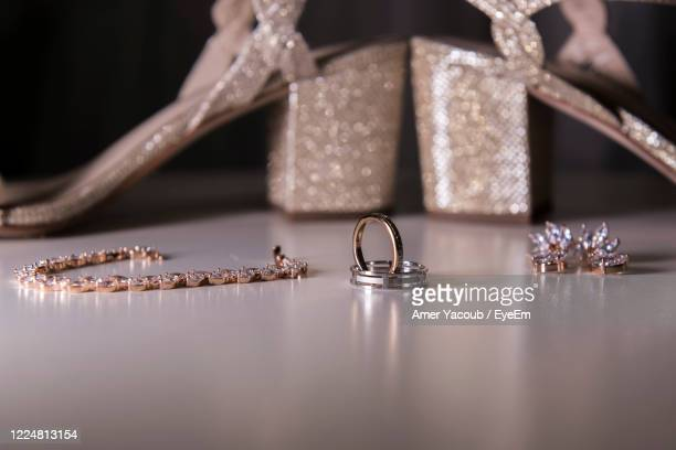 close-up of jewelry and sandals on table - silver shoe stock pictures, royalty-free photos & images