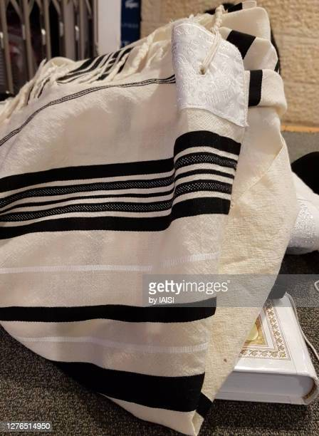 close-up of jewish prayer shawl / tallit with black stripes according to the orthodox ashkenazic tradition, and prayer book, vertical format - jewish prayer shawl stock pictures, royalty-free photos & images