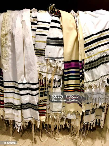 close-up of jewish prayer shawls on rack in store - jewish prayer shawl ストックフォトと画像