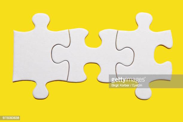 close-up of jigsaw piece on yellow background - jigsaw piece stock pictures, royalty-free photos & images