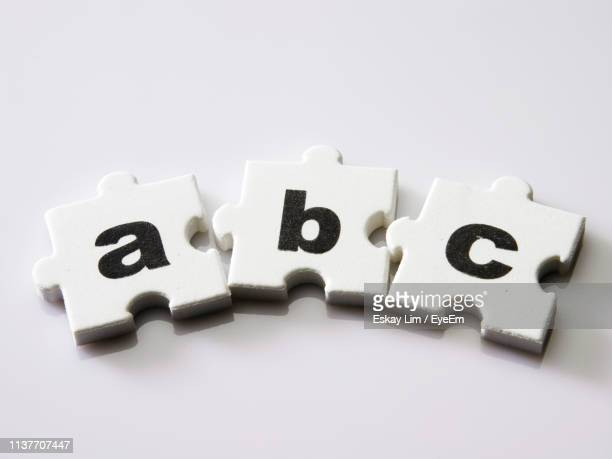 Close-Up Of Jigsaw Pieces With Text On White Background