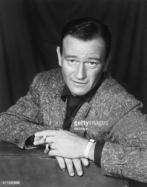 Closeup of John Wayne American actor. He is shown seated, facing the back of the couch on which he is seated. Ca. 1940s-1950s.