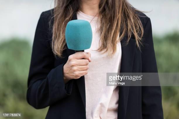close-up of journalist woman holding a microphone - stock photo - journalist stockfoto's en -beelden