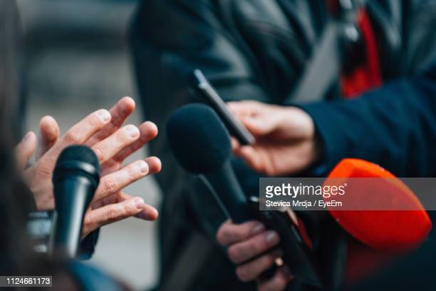 close-up of journalists holding microphone while taking interview - journalist stock pictures, royalty-free photos & images