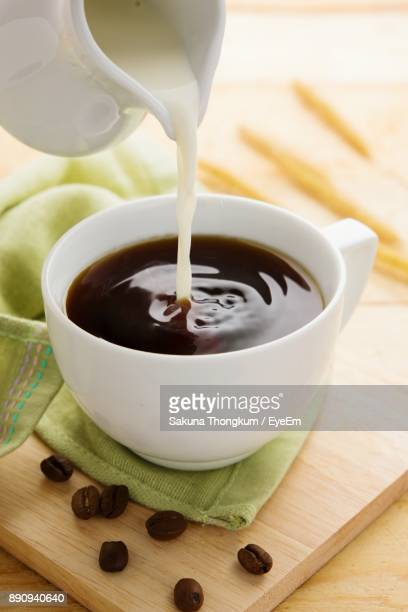 close-up of jug pouring milk in coffee on table - milk pour stock photos and pictures