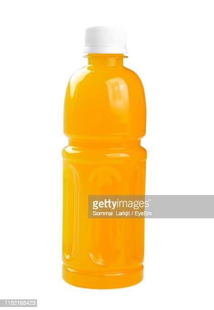 close-up of juice bottle against white background - orange juice stock pictures, royalty-free photos & images