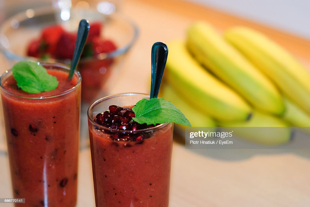 Close-Up Of Juices By Bananas On Table : Stock Photo