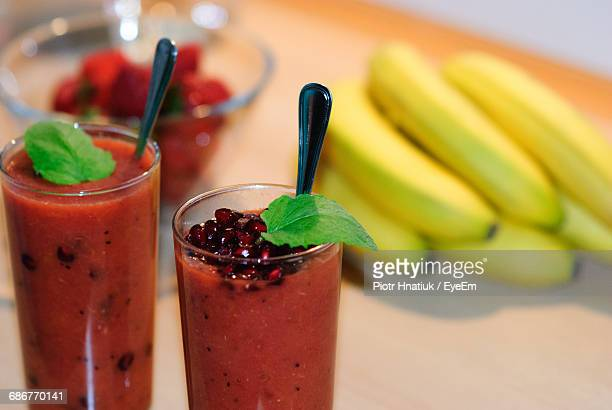 Close-Up Of Juices By Bananas On Table