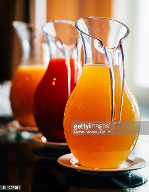 Close-Up Of Juices In Jugs On Table