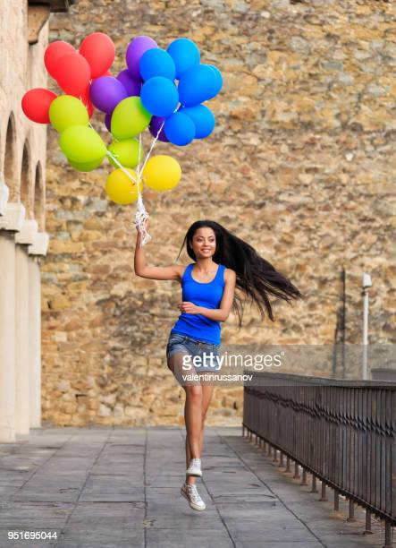 Close-up springen junge Frau mit bunten Luftballons