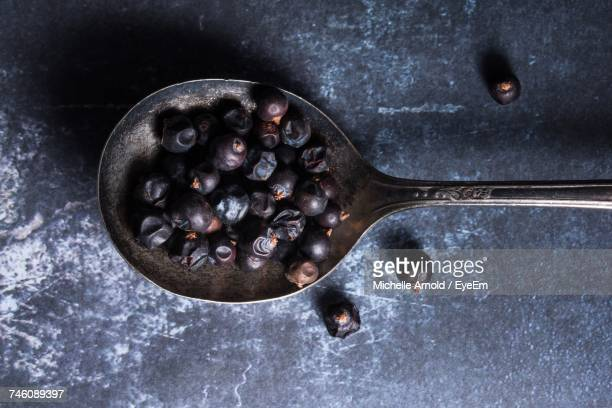 Close-Up Of Juniper Berries In Old Fashioned Spoon On Table