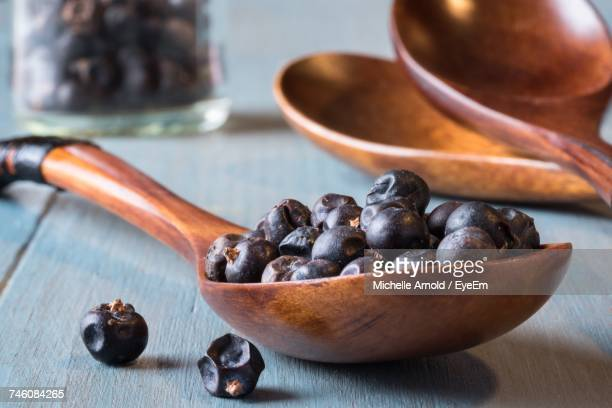 Close-Up Of Juniper Berries In Wooden Spoon On Table