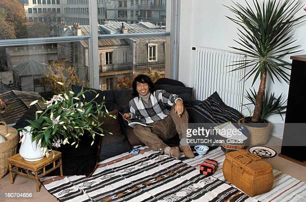 Closeup Of Kenzo Takada En novembre 1975 dans une pièce devant une baie vitrée assis sur des coussins entourés de plantes le styliste KENZO Takada...