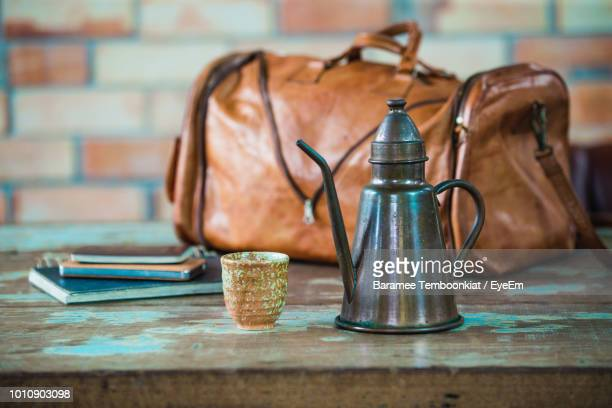 close-up of kettle and container against bag on table - やかん ストックフォトと画像