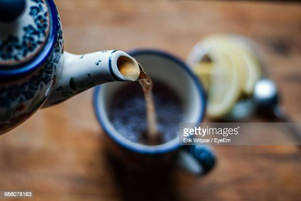 close-up of kettle pouring tea in cup - hot tea stock pictures, royalty-free photos & images