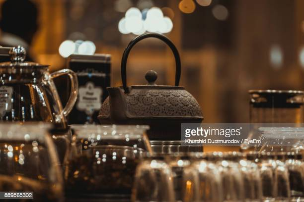 Close-Up Of Kettle With Drinking Glasses On Table