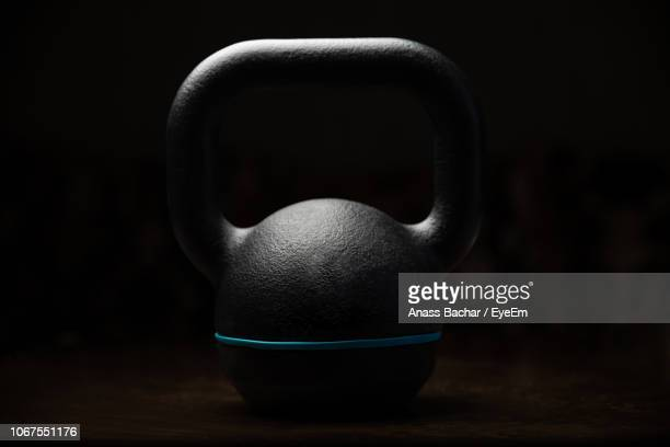 close-up of kettlebell on table against black background - sportgerät stock-fotos und bilder