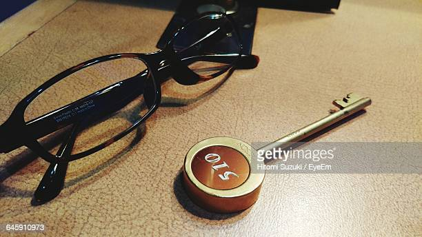 Close-Up Of Key And Eyeglasses On Table