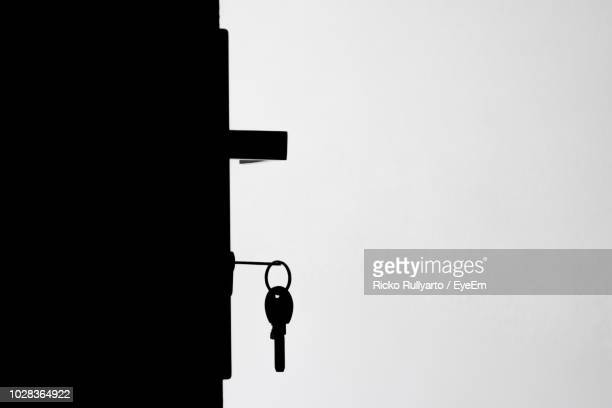 close-up of key hanging on door against wall - key ring stock photos and pictures