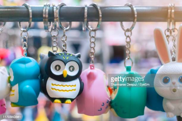 close-up of key rings hanging for sale at market stall - キーホルダー ストックフォトと画像