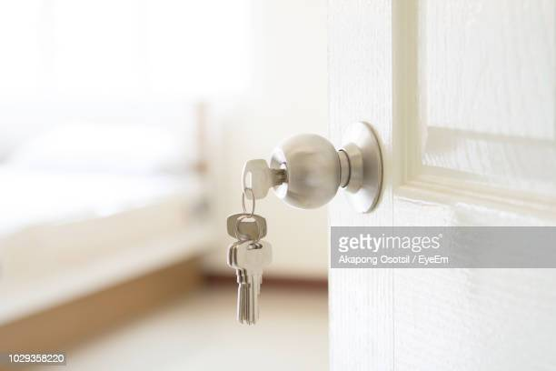close-up of keys hanging from doorknob - house key stock photos and pictures