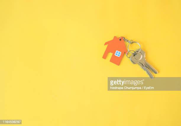 close-up of keys on yellow background - house key stock pictures, royalty-free photos & images