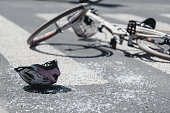 Closeup of kid's helmet and bike on a pedestrian lines after danger incident with a car