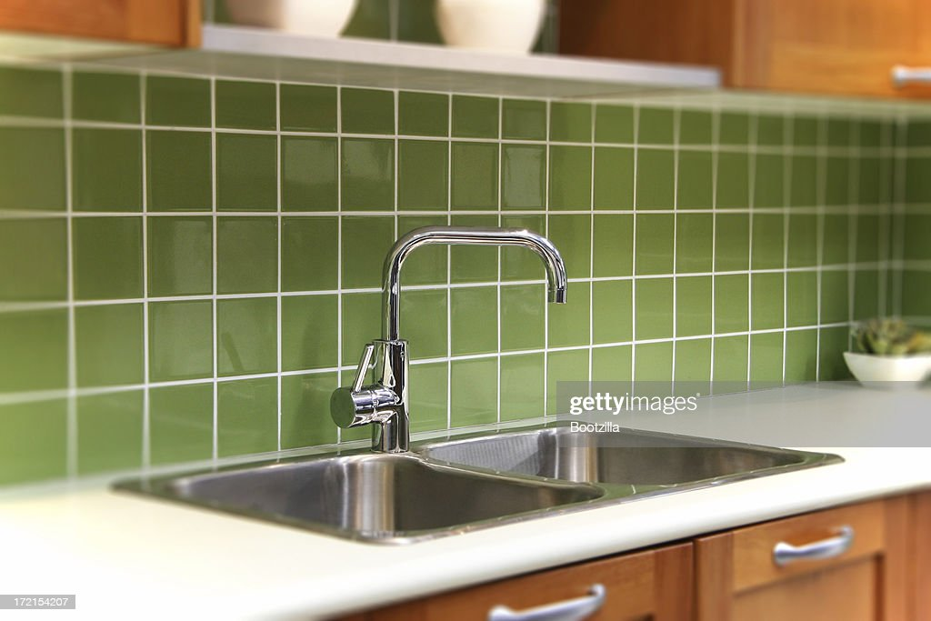 Close-up of kitchen sink with green splash board : Stock Photo
