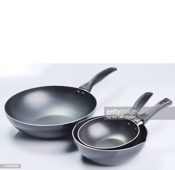 close-up of kitchen utensils on table against white background - saucepan stock pictures, royalty-free photos & images
