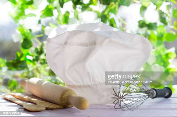 close-up of kitchen utensils with chef hat on table against plants - chef's hat stock pictures, royalty-free photos & images