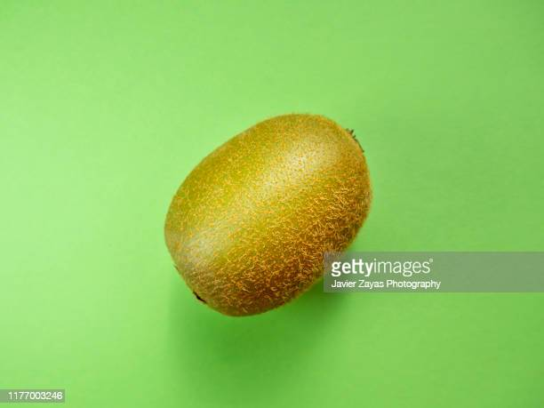 close-up of kiwi against green background - kiwi fruit stock pictures, royalty-free photos & images