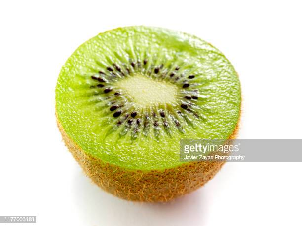 close-up of kiwi half over white background - juicy stock pictures, royalty-free photos & images