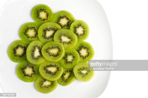 close-up of kiwi slices in plate on white background - kiwi fruit stock pictures, royalty-free photos & images