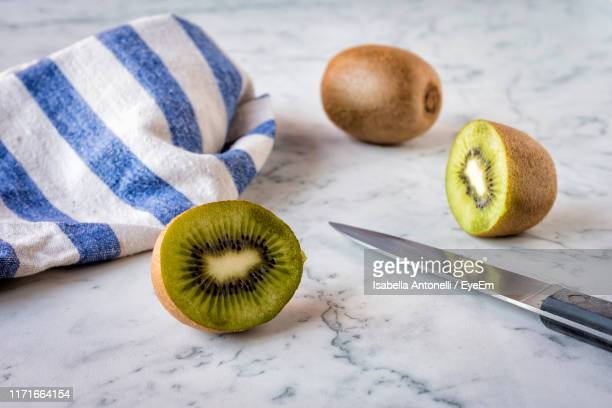 close-up of kiwis by knife and napkin on table - kiwi fruit stock pictures, royalty-free photos & images