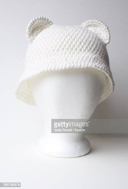 Close-Up Of Knit Hat In Figurine Against White Background