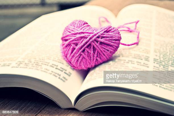 Close-Up Of Knitted Pink Heart On Open Book