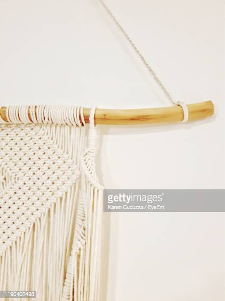 close-up of knitted strings hanging against white wall - かぎ針編み ストックフォトと画像