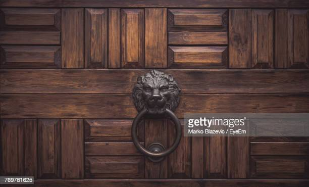 close-up of knocker on wooden door - door knocker stock photos and pictures